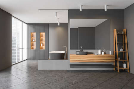 Gray and wooden bathing room interior with bathtub and shelf with accessories. Tiled floor and mirror with sink, rack with gels and bottles. Windows with city view, 3D rendering Imagens