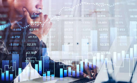 African American businessman or stock trader analyzing stock graph chart using laptop to buy or sell shares, side view portrait. Internet trading concept.