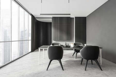 Stylish and gray interior of dining room with design table and four chairs. Minimalist style of home decor. concrete floor. Panoramic window with city view. 3d rendering Imagens