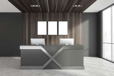 Interior of Scandinavian style office with gray and wooden walls, concrete floor and reception counter with two computers standing on it. Three mock up vertical posters, blurry cityscape. 3d rendering