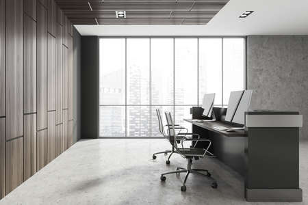 Side view of minimalistic Scandinavian style office with gray and wooden walls, concrete floor and reception counter with two computers standing on it. Window with blurry cityscape. 3d rendering