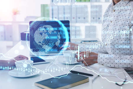 Businesswomen with laptop in office room, earth hologram and chart with numbers. Double exposure of lines and graphs. Concept of coffee break in office