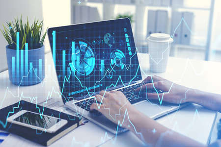 Office woman working with laptop in office room, tools and phone. Stock market changes, business bar chart and hud on laptop with statistics. Concept of online trading