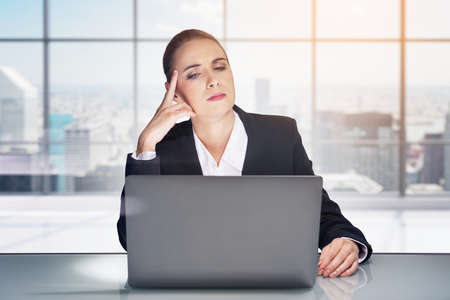 Office woman with a pensive look at the screen, windows with city buildings. Concept of business worker, secretary in international company. Concept of challenge Zdjęcie Seryjne