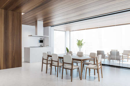 Corner of stylish dining room with white walls, concrete floor, long wooden table with white chairs and living room in the background. Window with blurry cityscape. 3d rendering