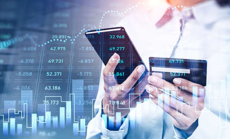Woman hands with smartphone and credit card, digital table with statistics and rising stock market. Online shopping, transactions. Concept of safe payment Stockfoto
