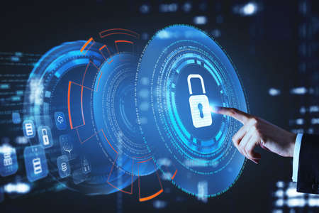 Businessman wearing formal suit is touching the hologram of digital interface with icon of padlock with his finger. City skyscrapers in the background. Concept of cloud data storage and security