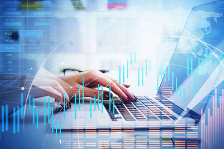 Businesswoman is typing message on laptop. Blurred office workplace with desk in the background. Financial chart and bar diagrams with map of the Earth in foreground. Concept of international trading