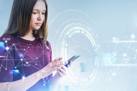 Businesswoman wearing purple sweater is holding smartphone with the hologram of digital interface. White background. Concept of future technologies in contemporary world 免版税图像