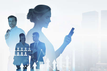 Group of business people work together to achieve the best results for their company. Smiling businesswoman with smartphone in the foreground. City skyscraper in the background. Concept of teamwork