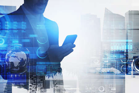 Businessman in formal suit is typing on smartphone with hologram of digital interface with globe, bar and pie diagrams. Singapore city skyscrapers in the background. Concept of cloud data storage