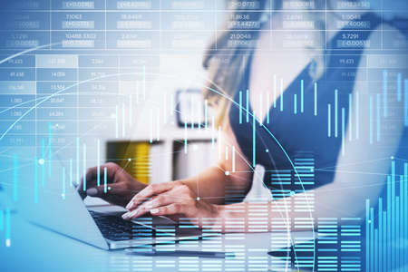 Businesswoman wearing black dress is typing on laptop. Blurred office workplace in background. Financial chart and bar diagrams with lines. Concept of international trading 免版税图像