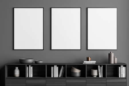 Row of three framed posters for your design in the gray living room. Interior with the wall and wooden sideboard. A concept of modern minimalist house. 3d rendering 免版税图像