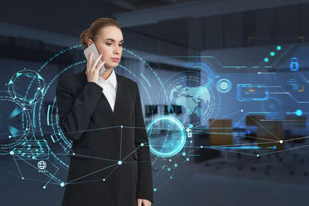 Attractive businesswoman wearing formal suit is talking via smartphone. Digital interface hud hologram with globe in the foreground. Office in the background. Concept of future technologies 免版税图像