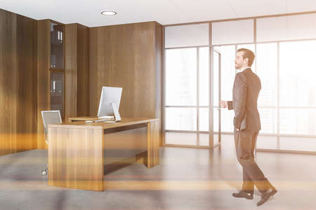 Businessman wearing formal suit is walking in hands in pocket pose inside office interior with panoramic window with city skyscraper, desktop, armchair, desk, shelf with folders and concrete floor