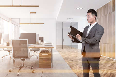 Businessman wearing formal suit is standing inside office interior and taking notes at clipboard. Panoramic window with city skyscraper, desktop, armchair, desk, concrete floor. Concept of director 免版税图像