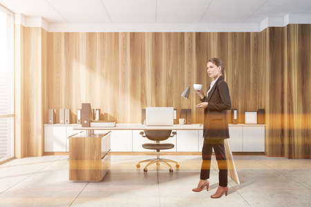 Businesswoman wearing formal suit is standing and drinking coffee inside office interior with panoramic window with skyscrapers, laptop, armchair, desk and concrete floor. Concept of director and ceo 免版税图像