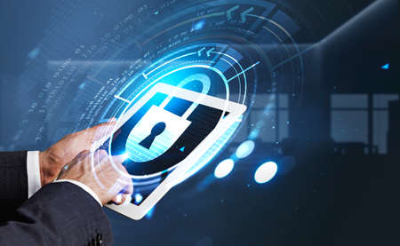 Businessman wearing formal suit is holding tablet with hologram of digital interface with icon of padlock. Blurred office workplace in the background. Concept of cloud data storage and security 免版税图像