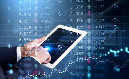 Businessman in formal suit is holding a tablet and touching it with his finger. Blurred office workplace in the background. Financial chart and graph in the foreground. Concept of successful trading