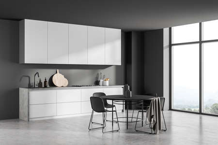 Modern gray interior design, using simple kitchen with original worktop, minimalist round black dining area, panoramic window and concrete floor. A concept of modern house. Corner view. 3d rendering