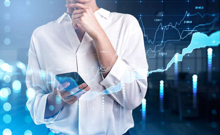Businesswoman wearing white shirt is holding smartphone. Blurred office workplace in the background. Financial chart and graph in the foreground. Concept of successful trading on stock market