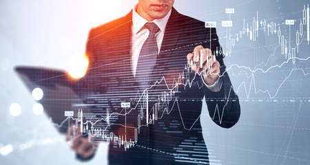 Businessman in formal suit is touching a financial chart with his finger. City skyscrapers in the background. Forex candlesticks in the foreground. Concept of successful trading strategy