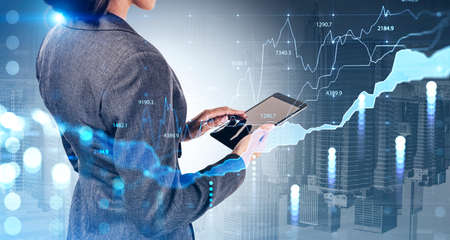Businesswoman in formal suit is holding a tablet and touching it with his finger. New York city skysrapers in the background. Financial chart and graph in the foreground. Concept of successful trading