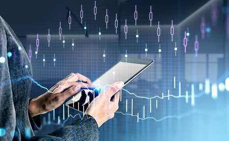 Businesswoman wearing formal suit is touching screen of tablet with finger. Blurred office in the background. Financial candlestick, chart and graph in foreground. Concept of trading on stock market 免版税图像