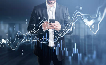 Businessman wearing formal suit is holding smartphone and typing message. Blurred office in the background. Financial chart and graph in the foreground. Concept of successful trading strategy