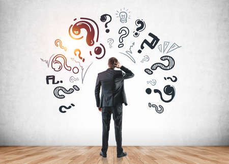 Thoughtful serious businesswoman wearing formal suit is touching his hand with a hand, standing in front of the wall with sketch with icons of question marks. Concept of thinking for business projects 免版税图像