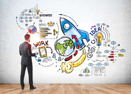 Businessman in formal suit near sketch with icons of rocket, light bulb, globe, bar and pie diagrams, teamwork, plan, smartphone, success, message, teamwork and cogwheels. Concept of creative idea