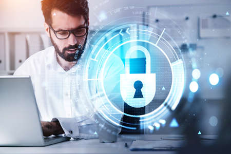 Businessman wearing white shirt is typing on laptop with hologram of digital interface with icon of padlock. Office workplace in the background. Concept of cloud data storage and security