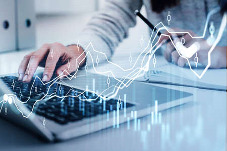 Businesswoman wearing white pullover is typing on laptop and taking notes. Office workplace in the background. Financial chart and graph in foreground. Concept of successful trading