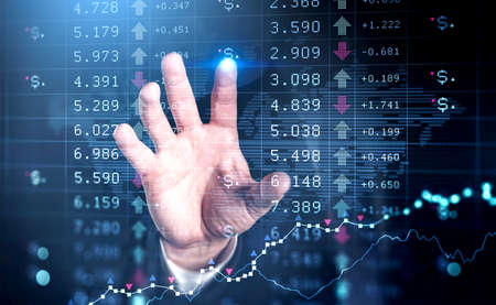 Businessman wearing formal suit is touching screen with chart with his finger. Dark blue background. Financial graph in the background. Concept of analyzing stock market behavior 免版税图像