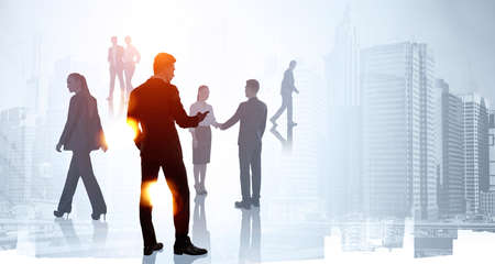 Silhouettes of group of business people work together, talking and shaking hand. Businessman with smartphone in foreground. Skyscraper in background. Concept of teamwork, cooperation and communication