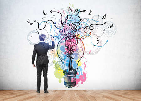 Businessman in formal suit is touching colorful pink, blue and yellow sketch with large light bulb, arrows, lines and cogwheels on concrete wall. Wooden floor. Concept of imagination and inspiration