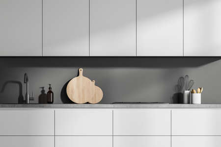 Interior with minimalist simple white kitchen cabinet, having gray worktop and backsplash. A concept of modern house design. 3d rendering 免版税图像