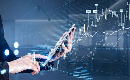Businesswoman wearing formal suit is touching screen of tablet with finger. Blurred office in th background. Forex candlestick, chart and graph in foreground. Concept of trading on stock market