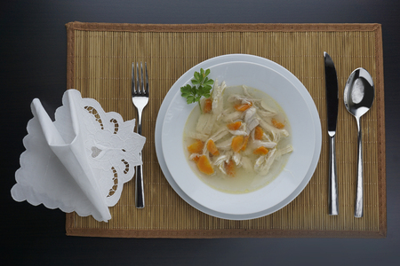 Chicken soup in a plate  arranged on a black table