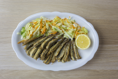 Fried anchovy with salad and lemon on a white plate