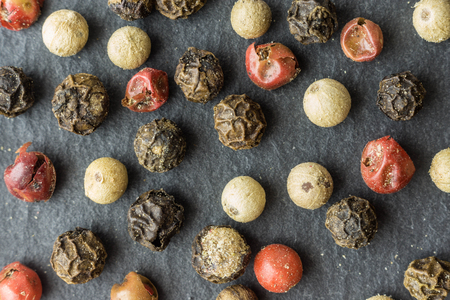 Colored Pepercorns on black stone background top view