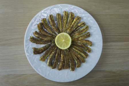 Fried anchovies in a round plate with lemon Reklamní fotografie