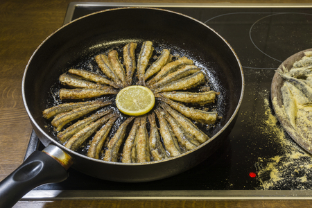 Anchovies fry in a pan