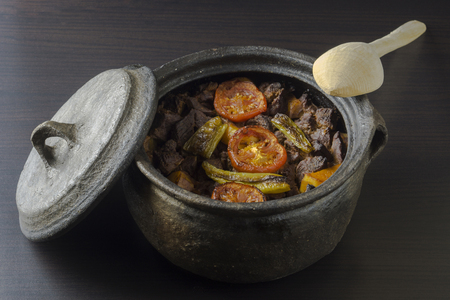 Stew in clay pot with wooden spoon
