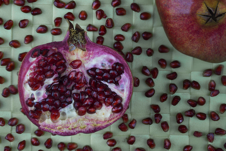 Pomegranate half with seeds on green background