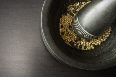 Mortal and pestle with spices on black wooden background