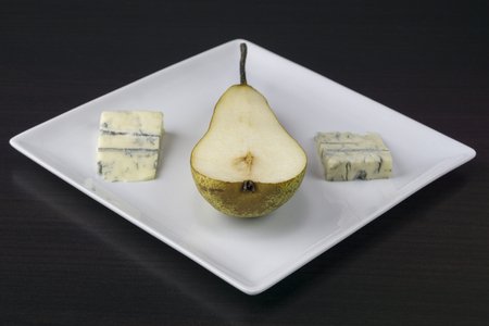 Pear helped with cheese in a plate on a dark background 写真素材