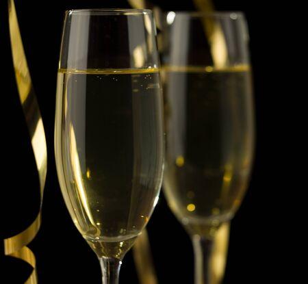 Dos copas de champán delante de un fondo oscuro