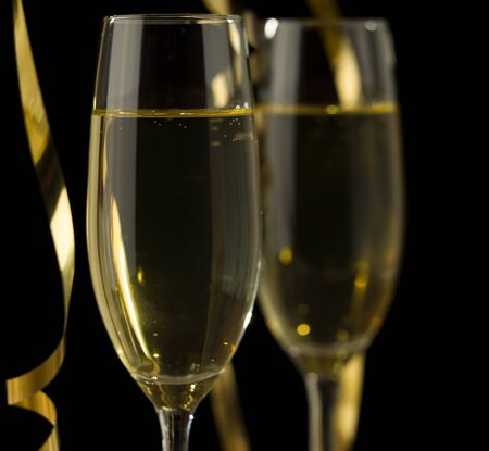 Two glasses of champagne in front of dark background
