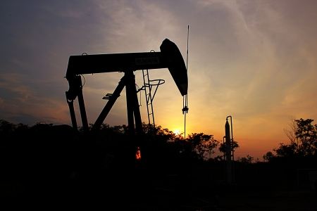 pumping: sunset at oil field behind pumping unit  Stock Photo